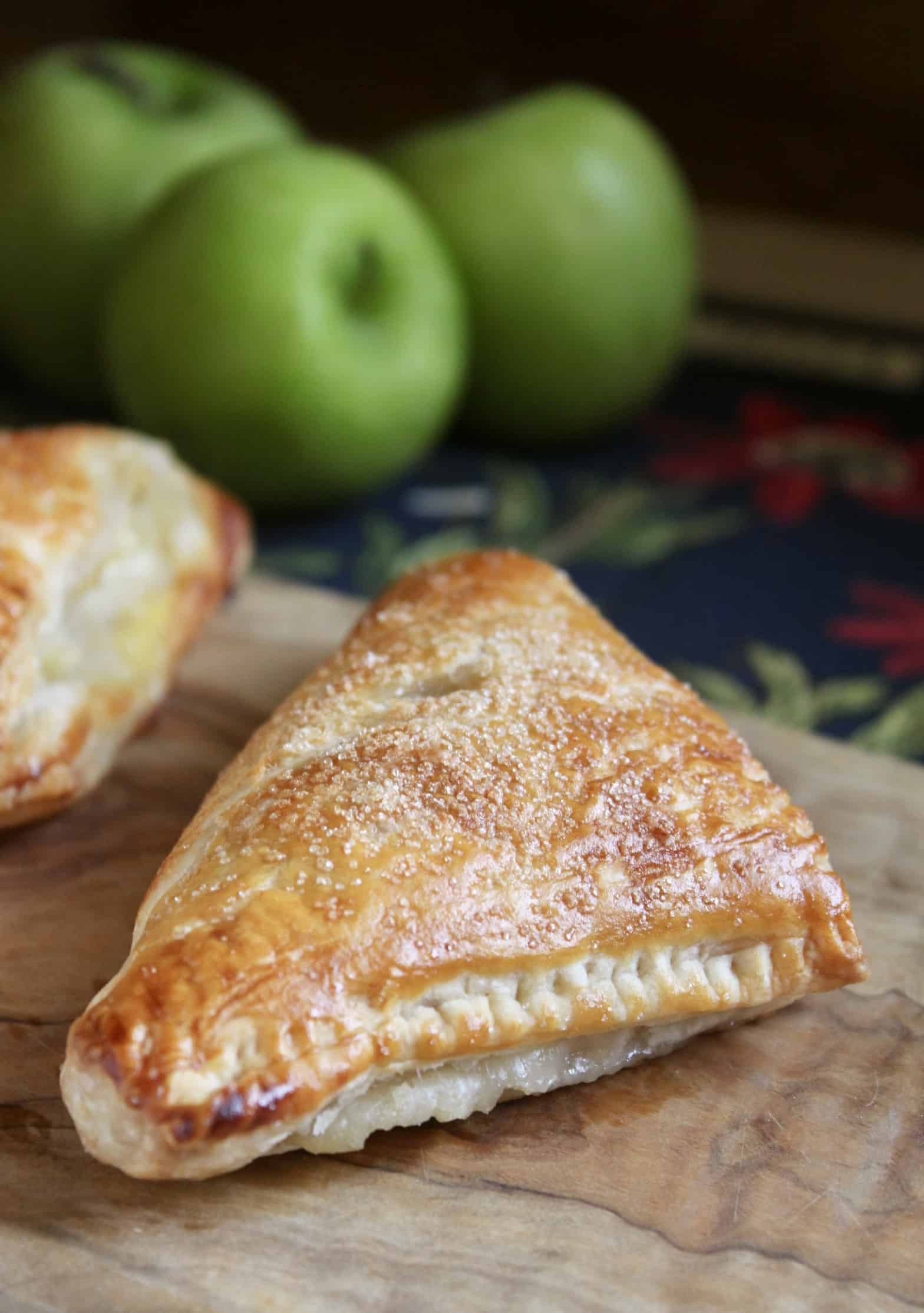 apple turnover on a board with green apples