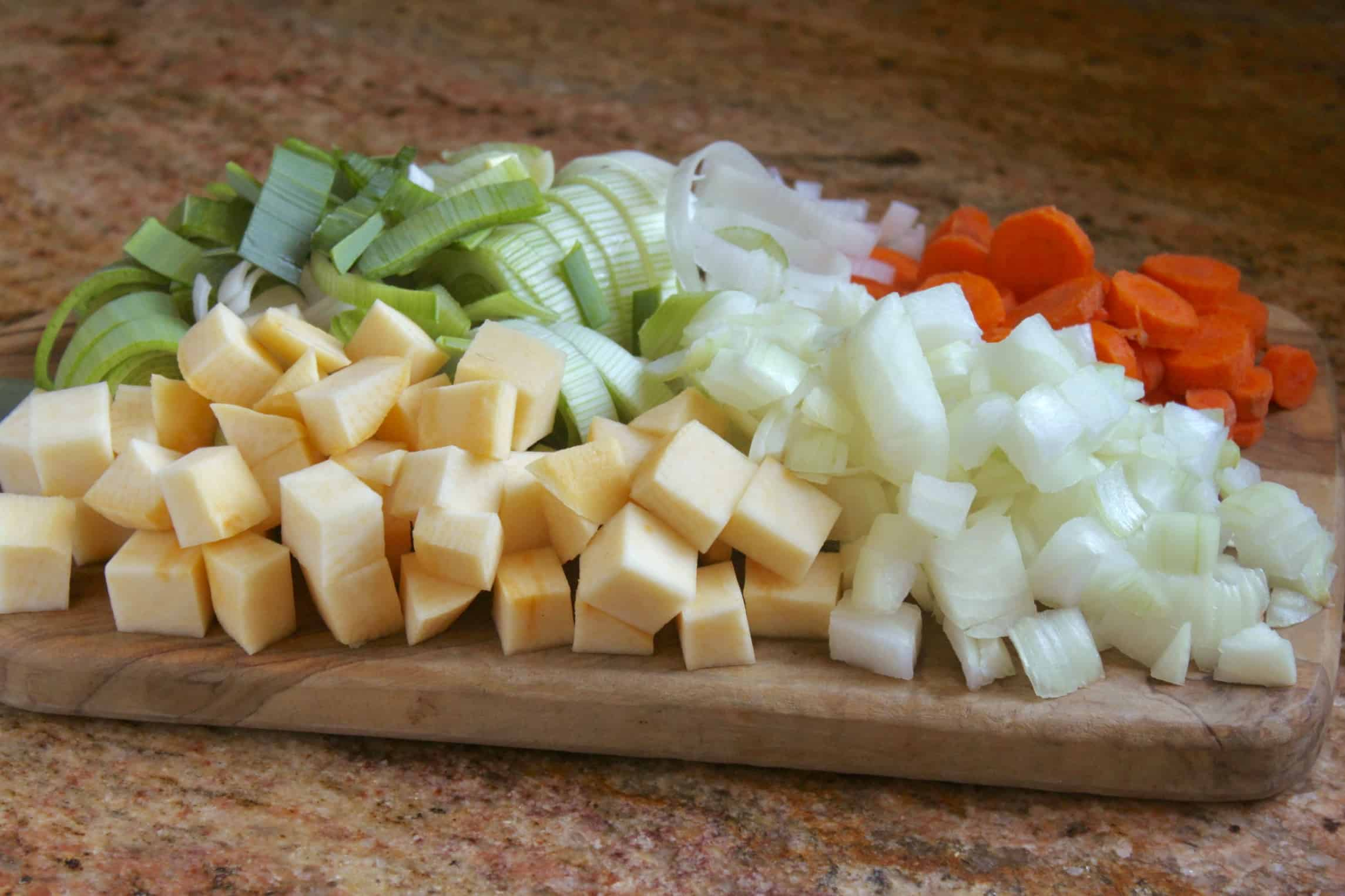 rutabaga, leeks, onion and carrots on a board