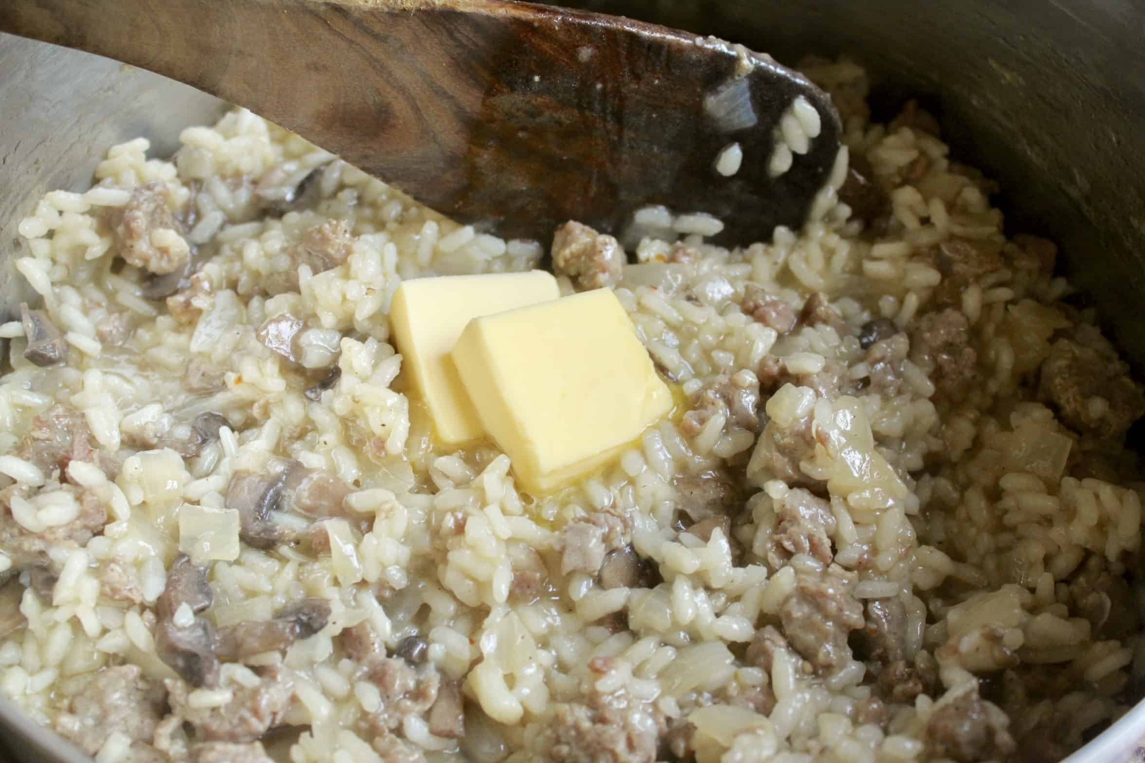 adding butter to sausage and mushroom risotto