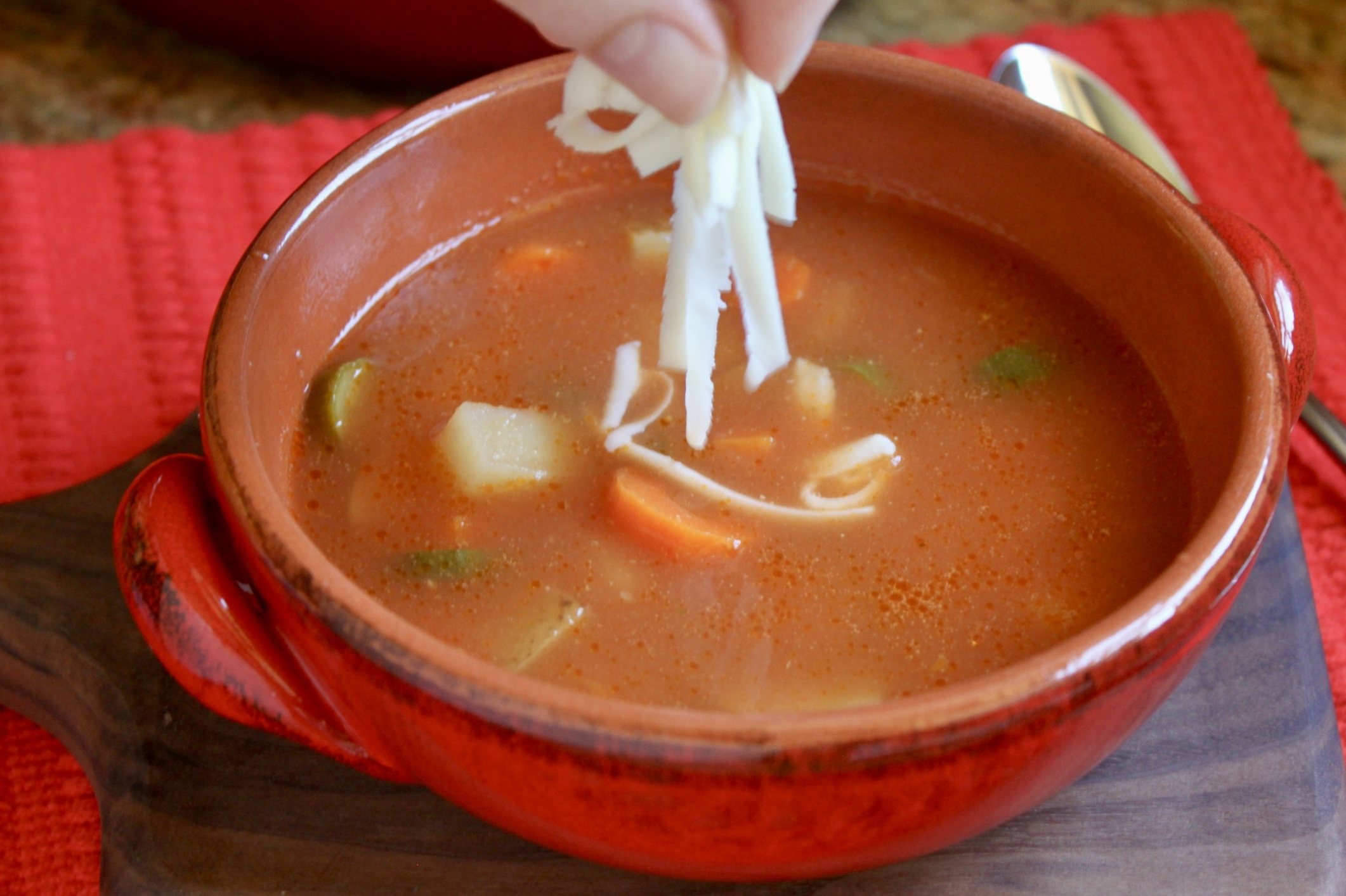 adding cheese to quick and easy tortilla soup