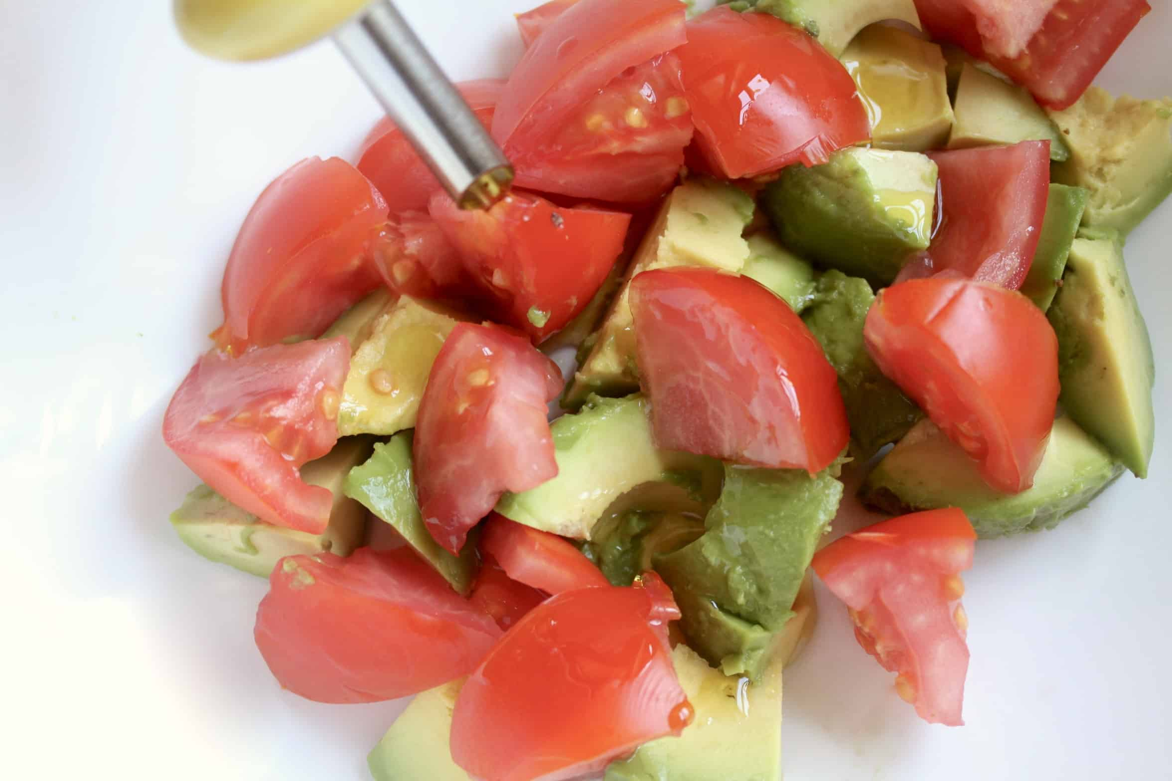adding olive oil to avocado and tomato salad