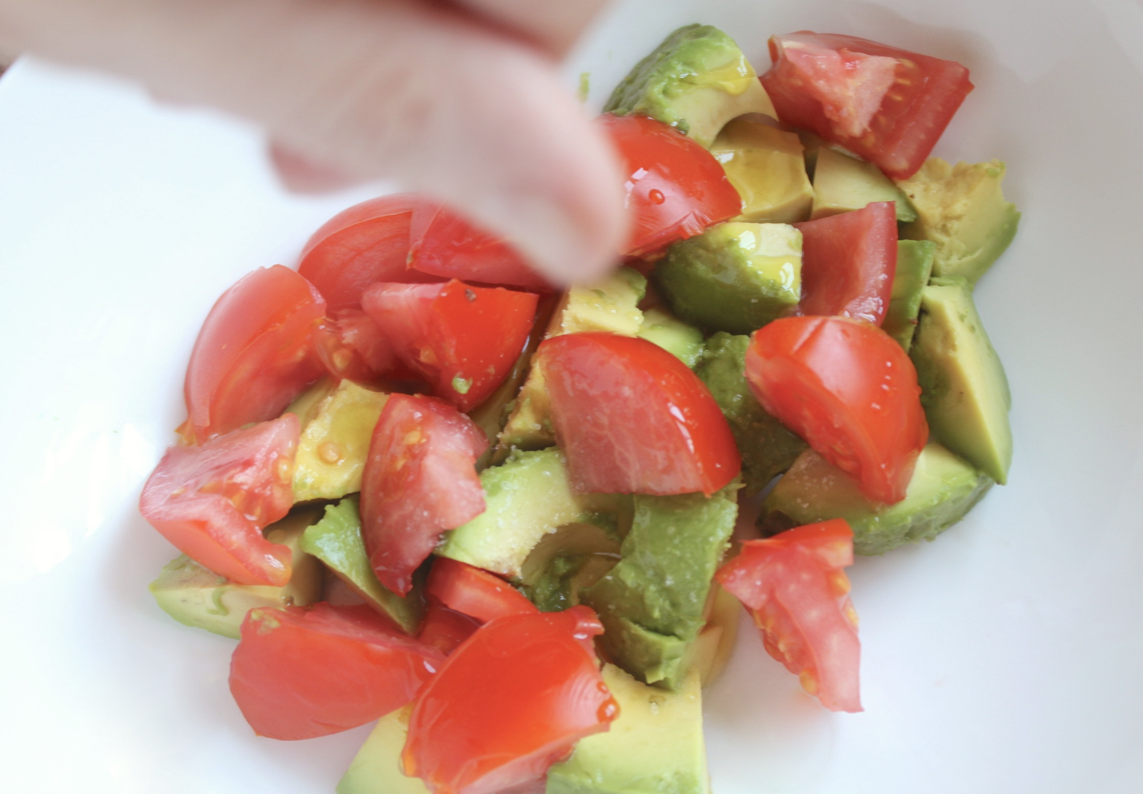 adding salt to avocado and tomato salad