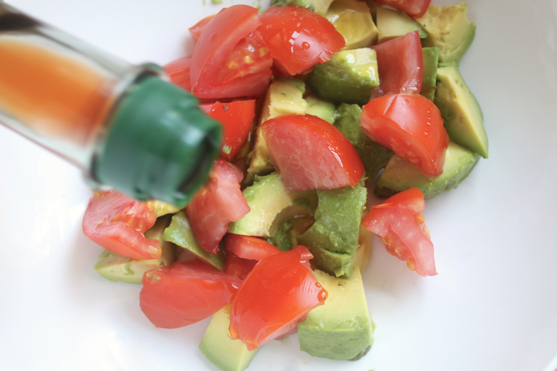 adding wine vinegar to avocado and tomato salad