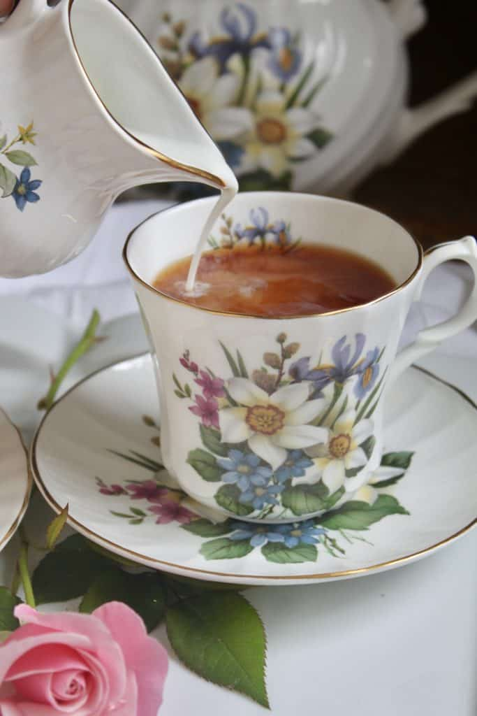 pouring milk into teacup to serve with afternoon tea scones