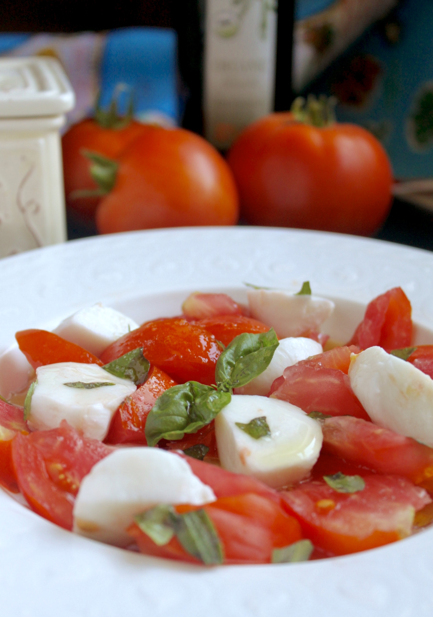 caprese salad with tomatoes in background