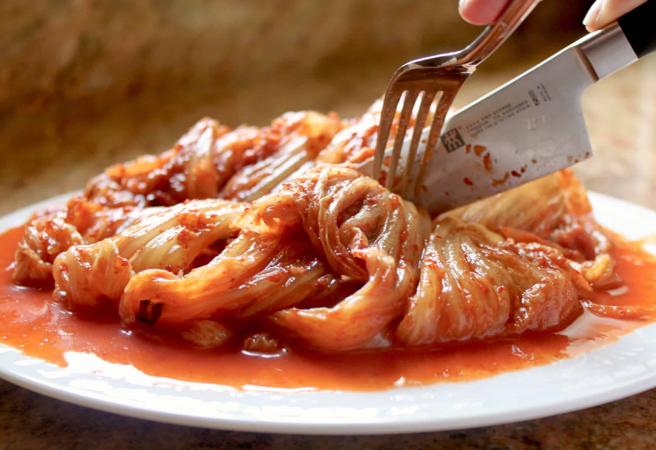 cutting kimchi on a plate