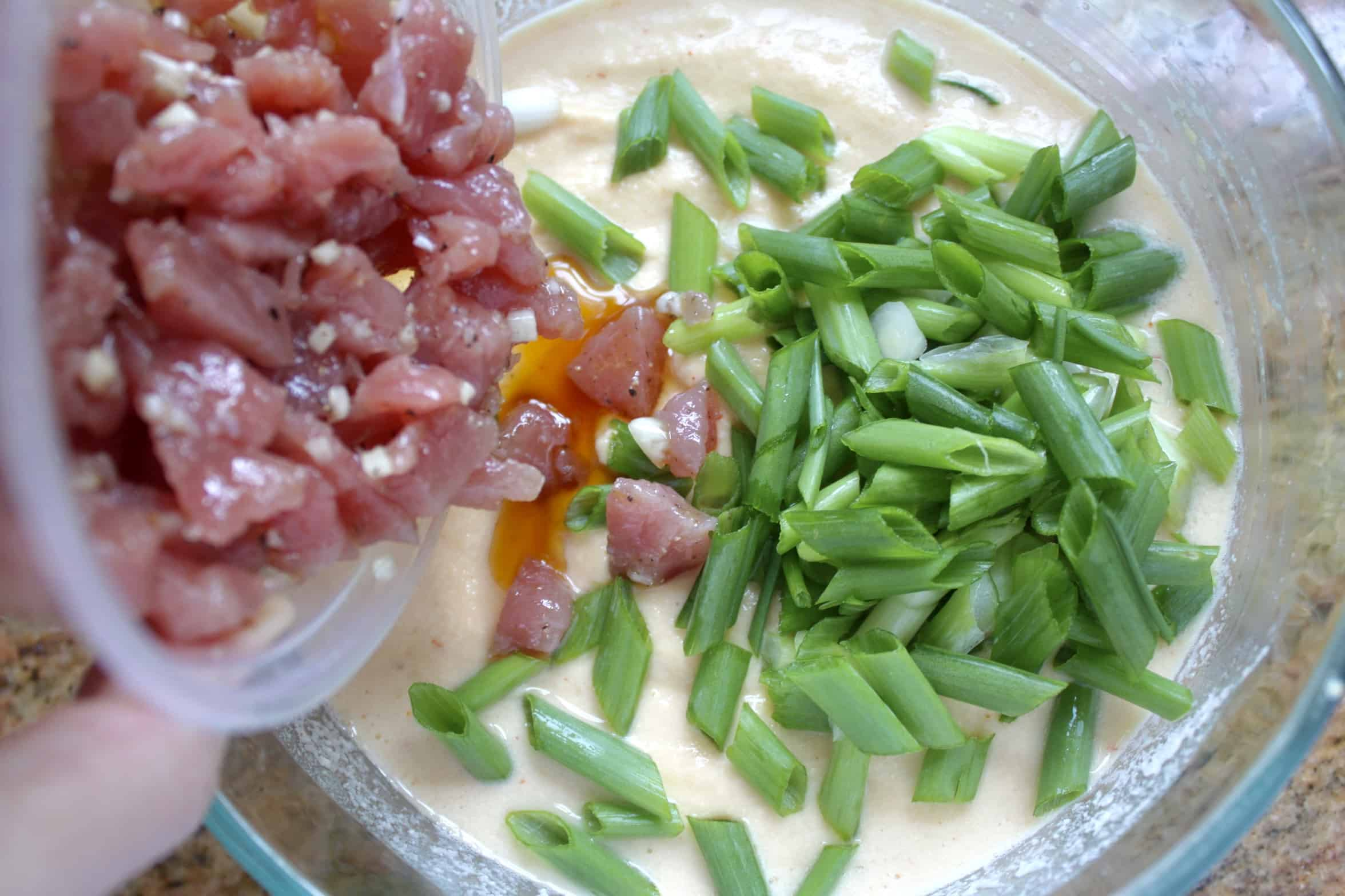 adding chopped pork to mung bean and green onion batter