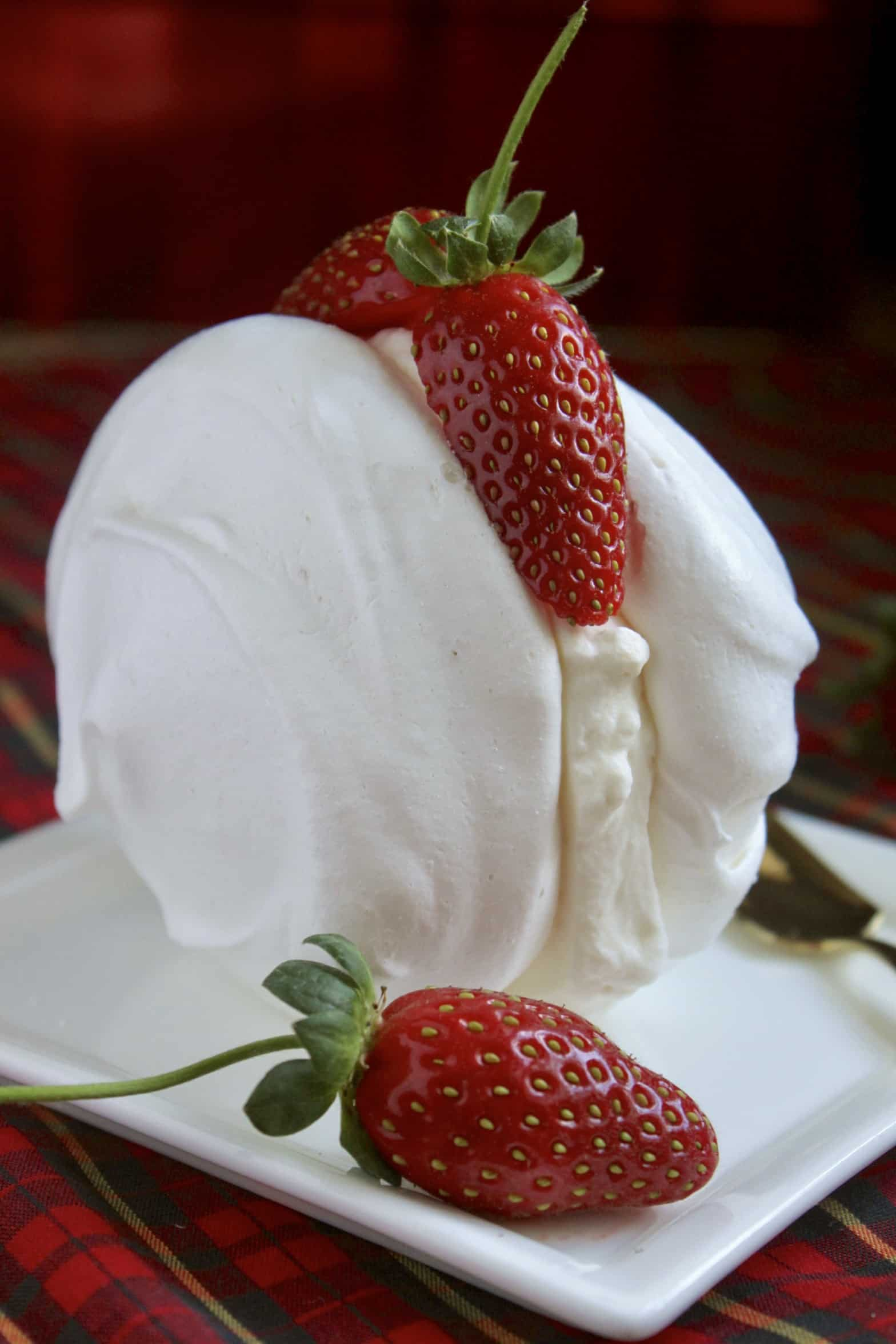 Meringues with cream and strawberries on a plate
