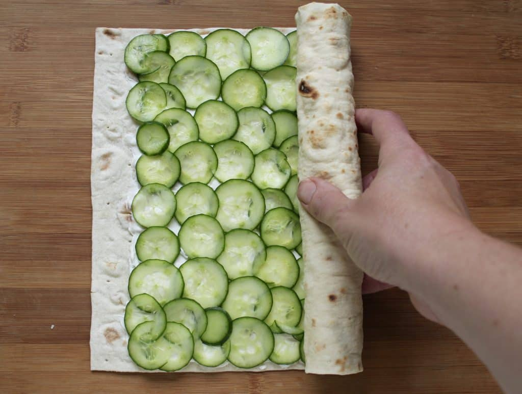making cucumber and cream cheese sandwich rolls