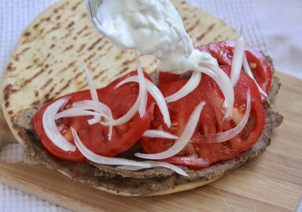 assembling a gyro with meat, tomatoes and onion