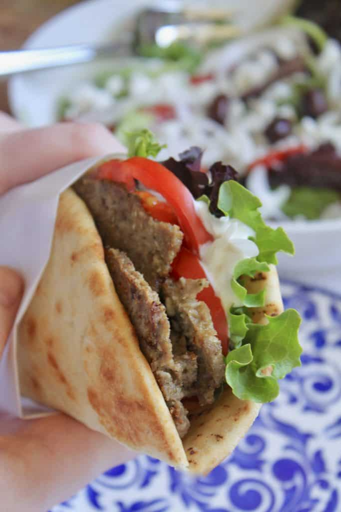 handheld homemade Greek gyro sandwich in a pita