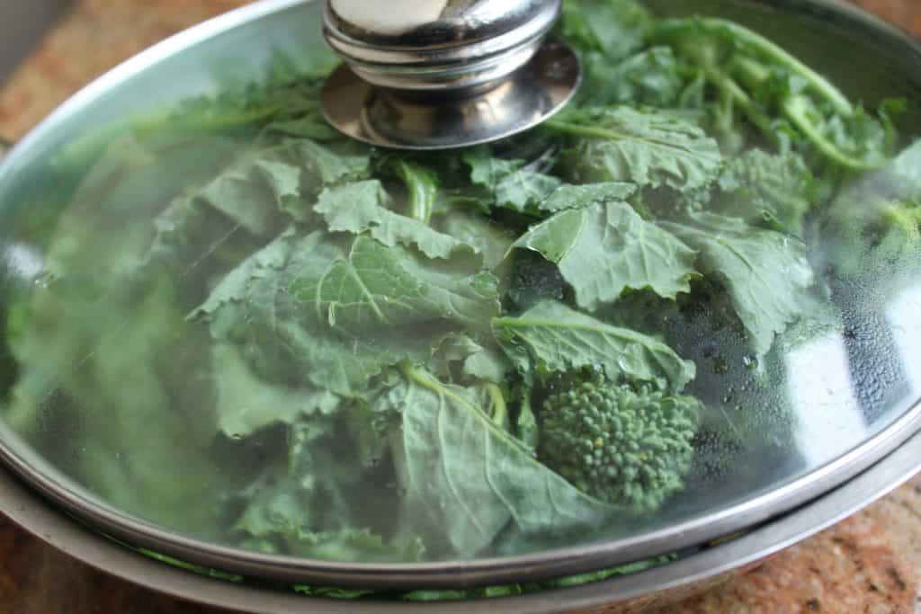 Rapini in a pan with glass lid