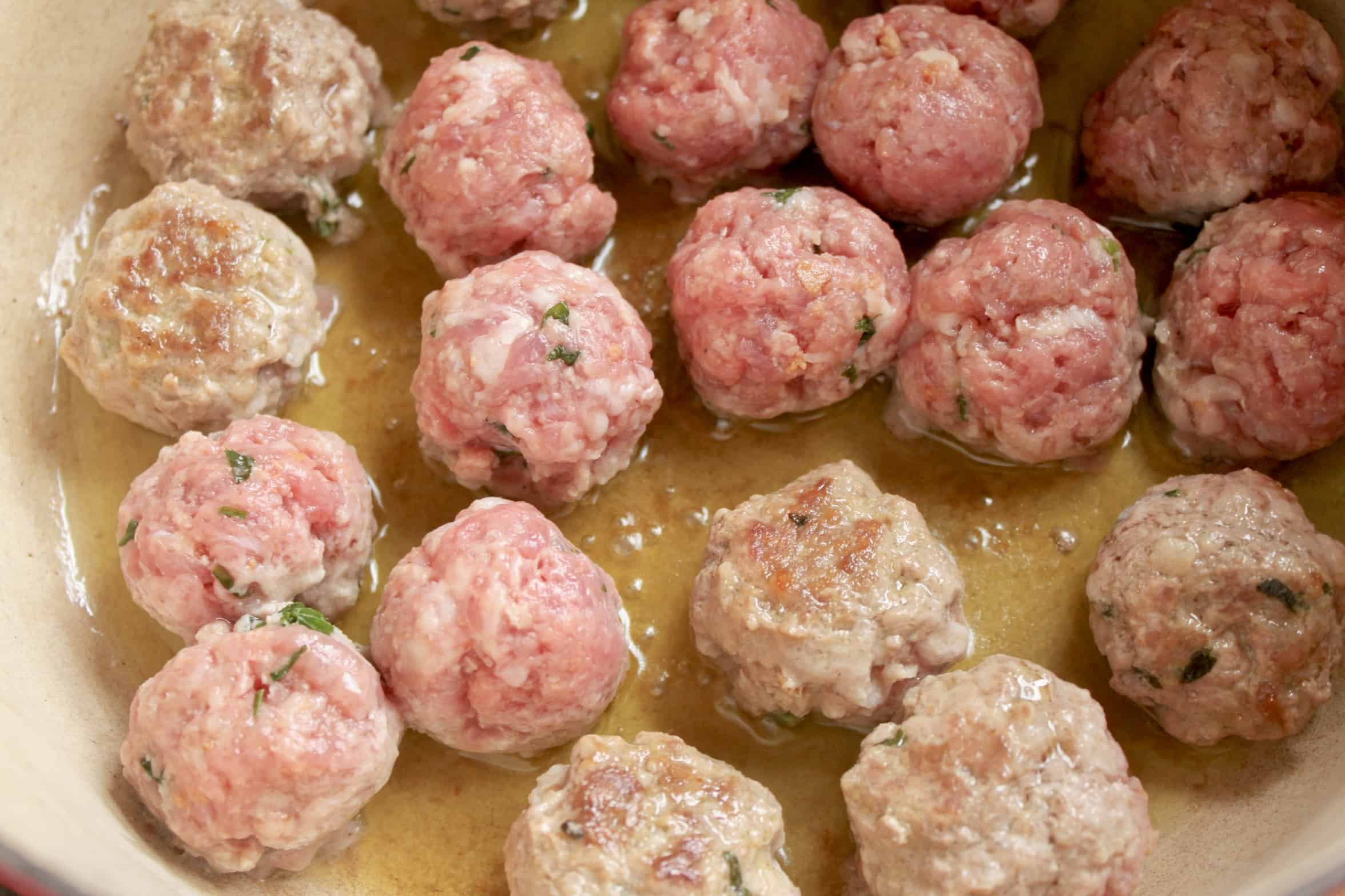 sauteeing meatballs in a pot