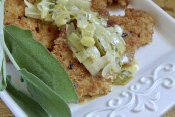 turkey cutlets with leeks and sage butter sauce on a platter with sage