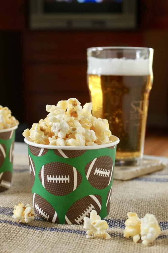 photo of caramel crunch popcorn in a paper cup with brown footballs on it with a beer behind