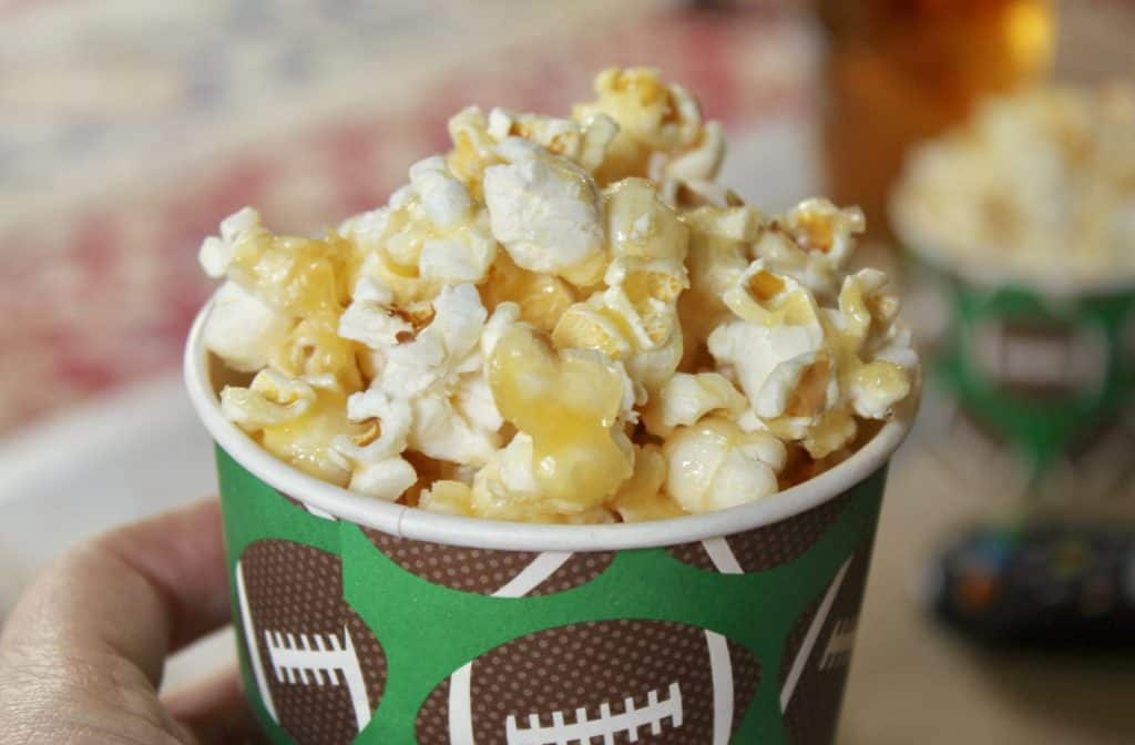 handheld cup of caramel crunch popcorn