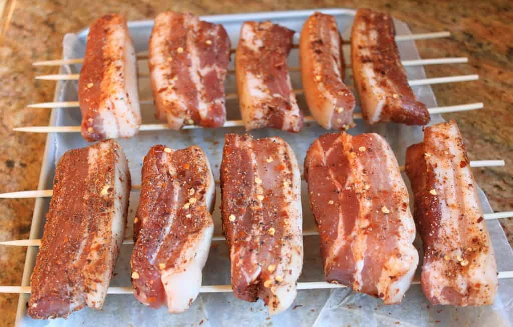 pork belly covered in pepper, ready to dry