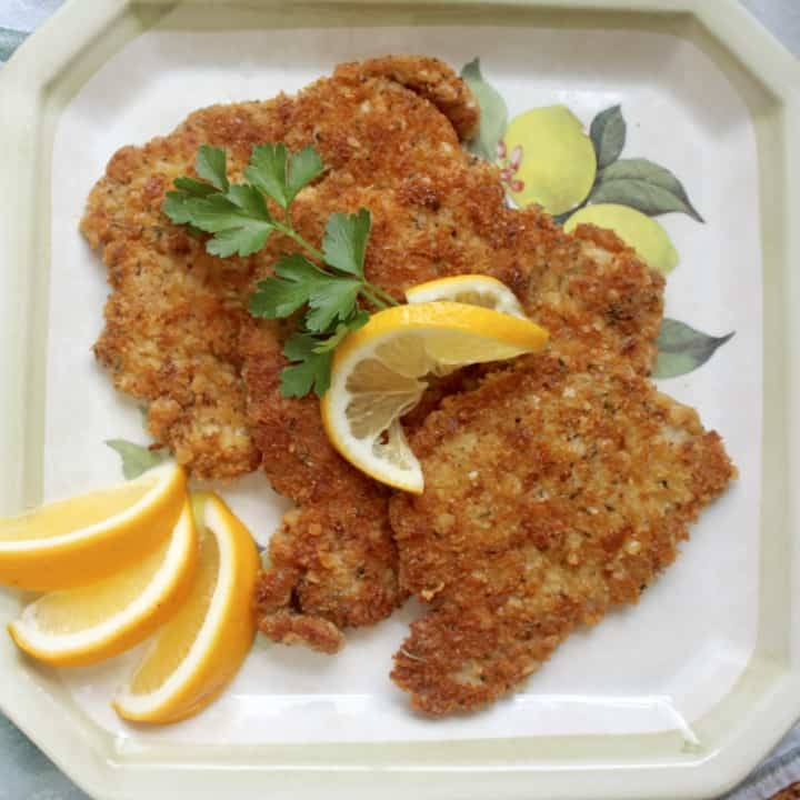 pork schnitzel on a plate with lemon slices