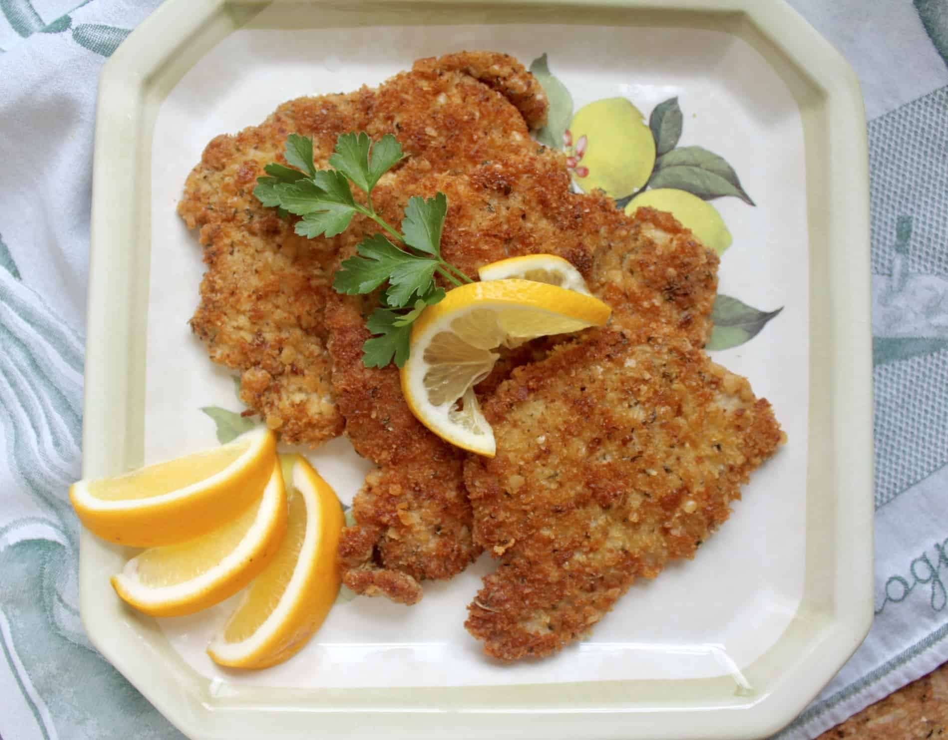 breaded pork schnitzel on a plate with lemon slices