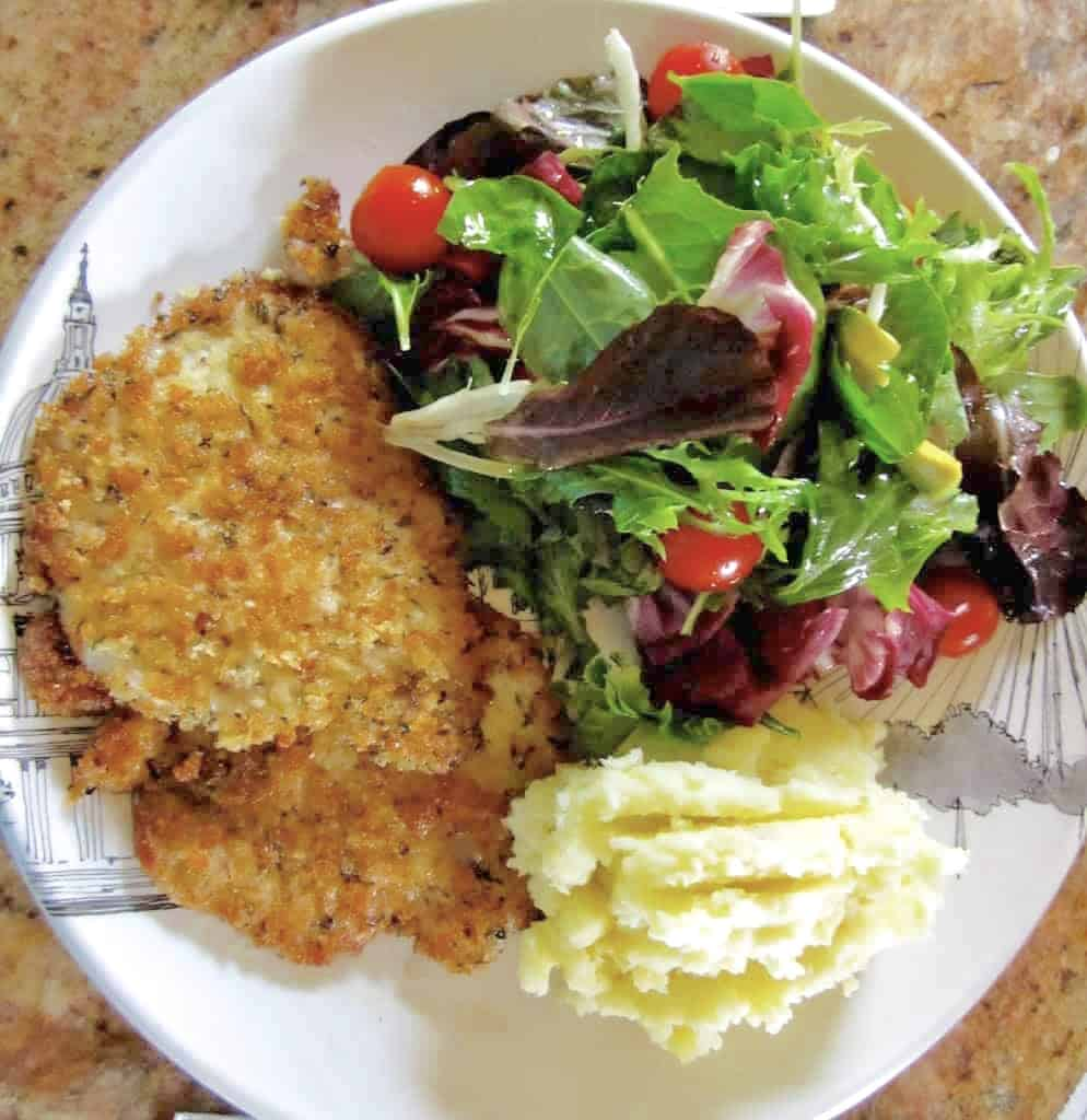 kids breaded pork schnitzel with salad and potatoes