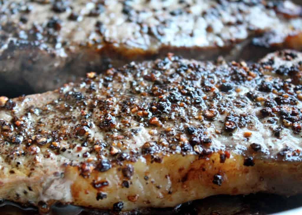 Steak au Poivre (Peppered Steak) sizzling in a pan
