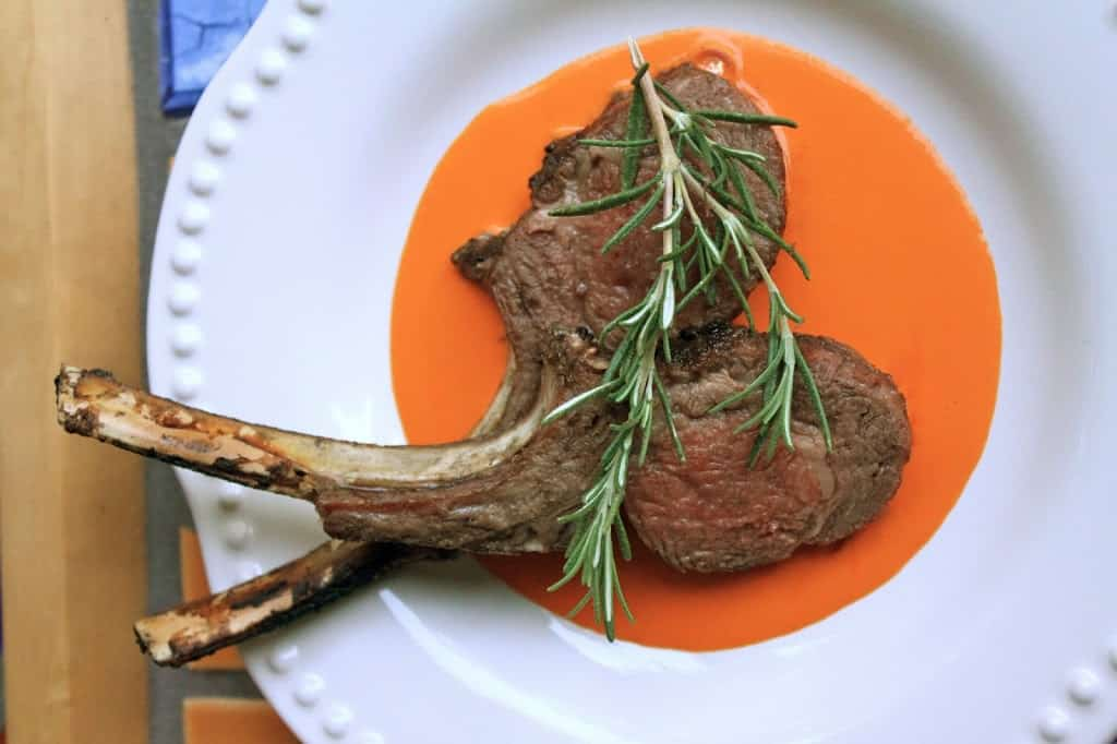 lamb chops on a plate with red pepper sauce and rosemary