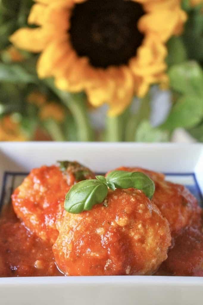 ricotta gnudi al sugo or ricotta dumplings with a sunflower in the background