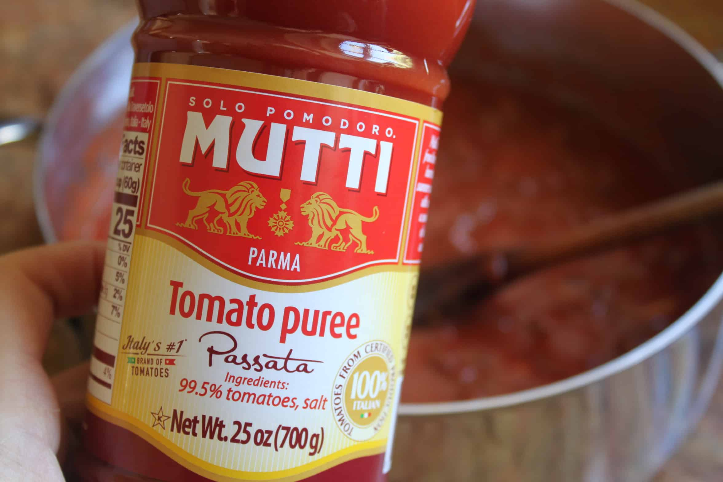 mutti tomato puree bottle in front of pan of sauce