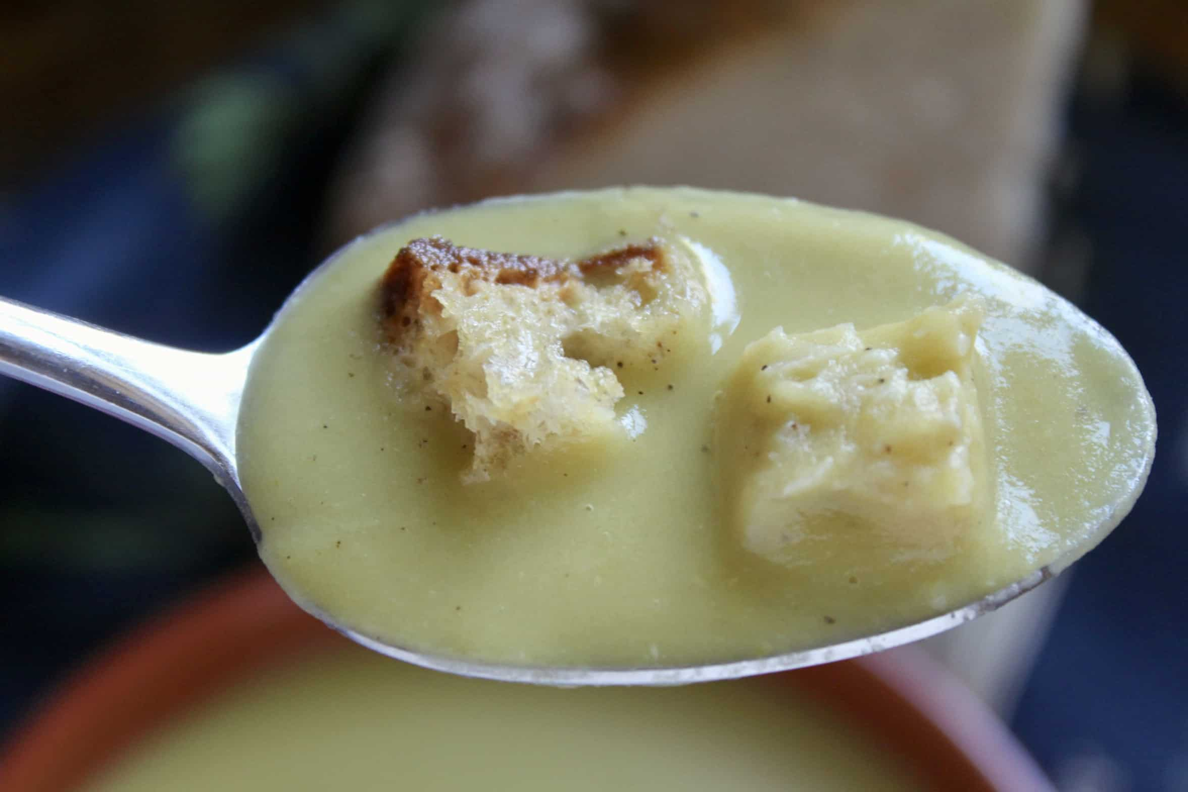 spoonful of pea soup with croutons