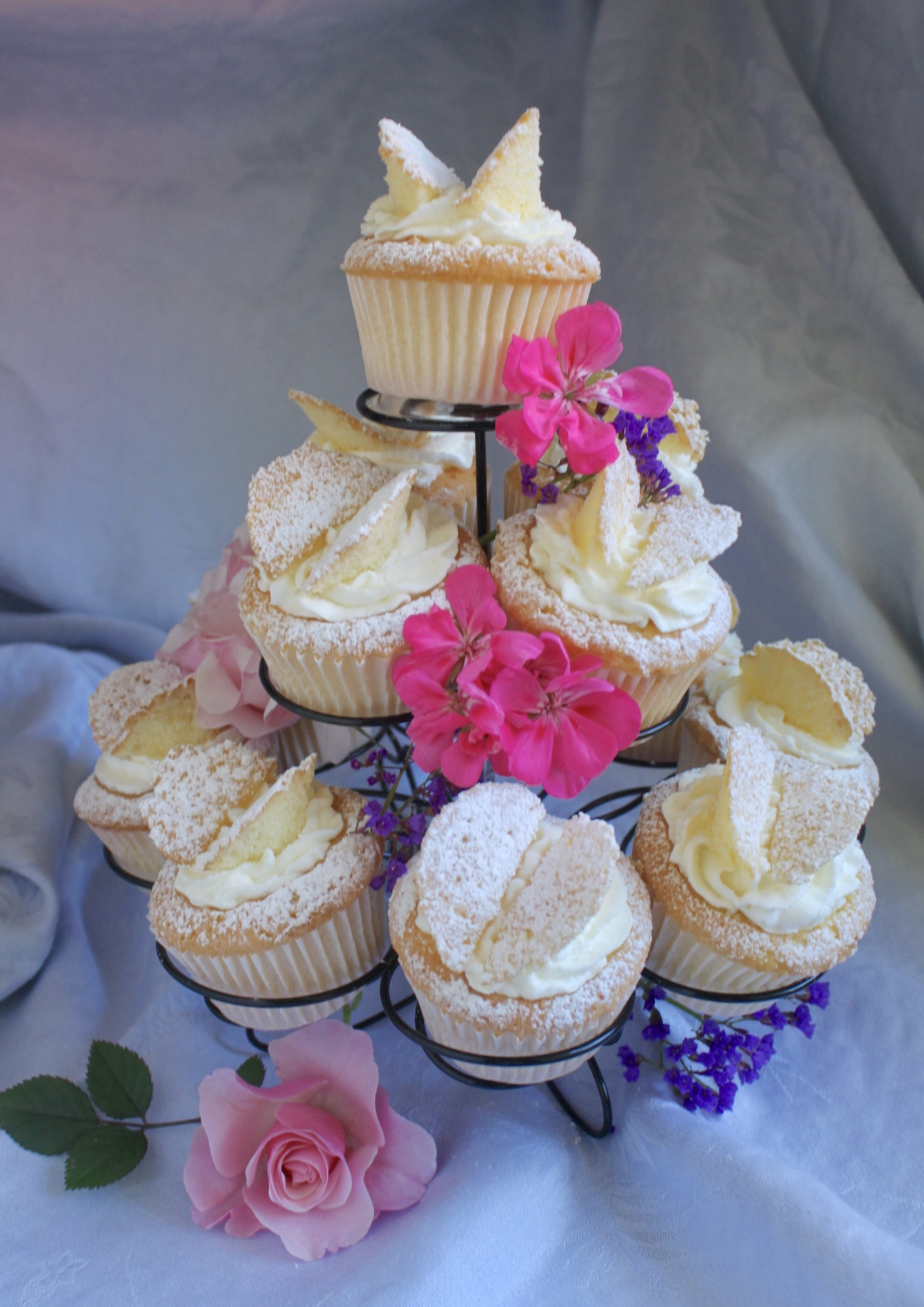 butterfly cupcakes on a stand with fresh flowers