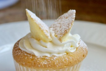 Butterfly cupcake with confectioner's sugar sifting onto it