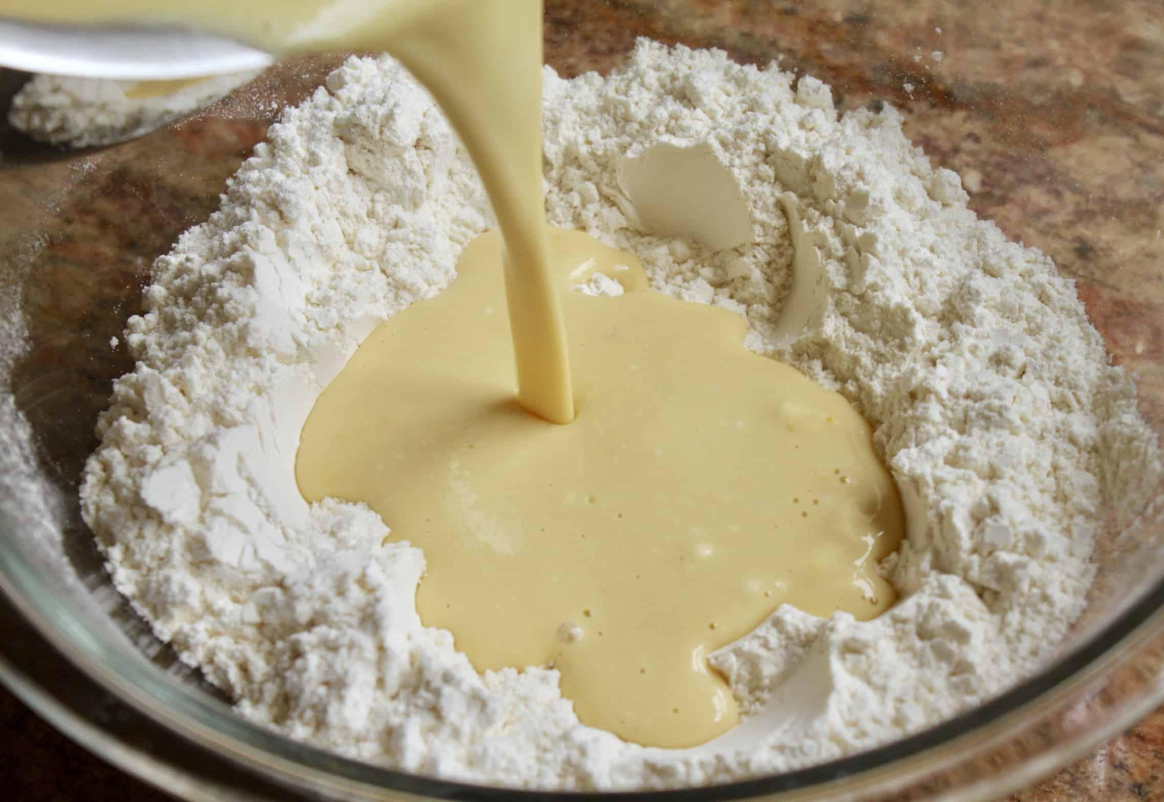 adding liquid to flour for pancakes