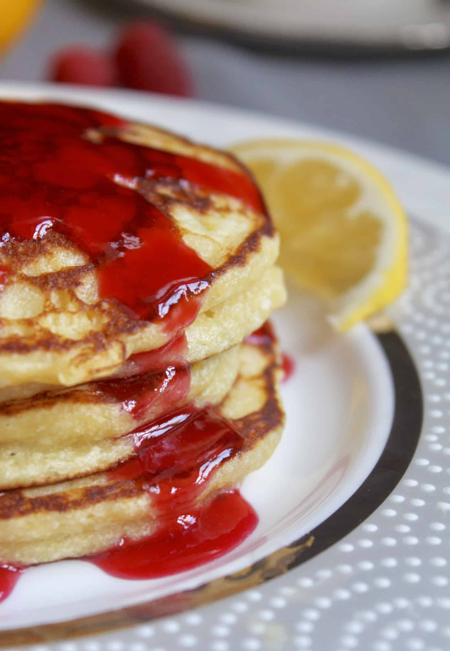 close up of lemon ricotta pancakes with raspberry syrup dripping down