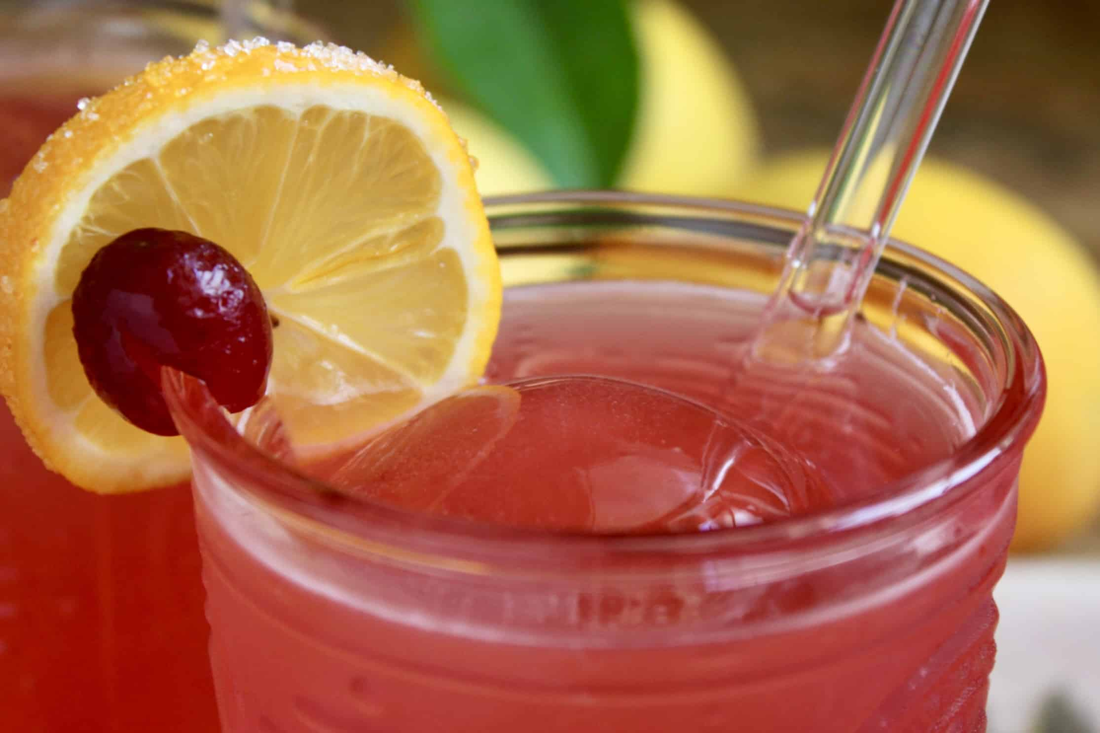 glass of cranberry lemonade with garnish and straw
