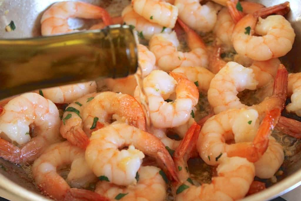 adding wine to shrimp
