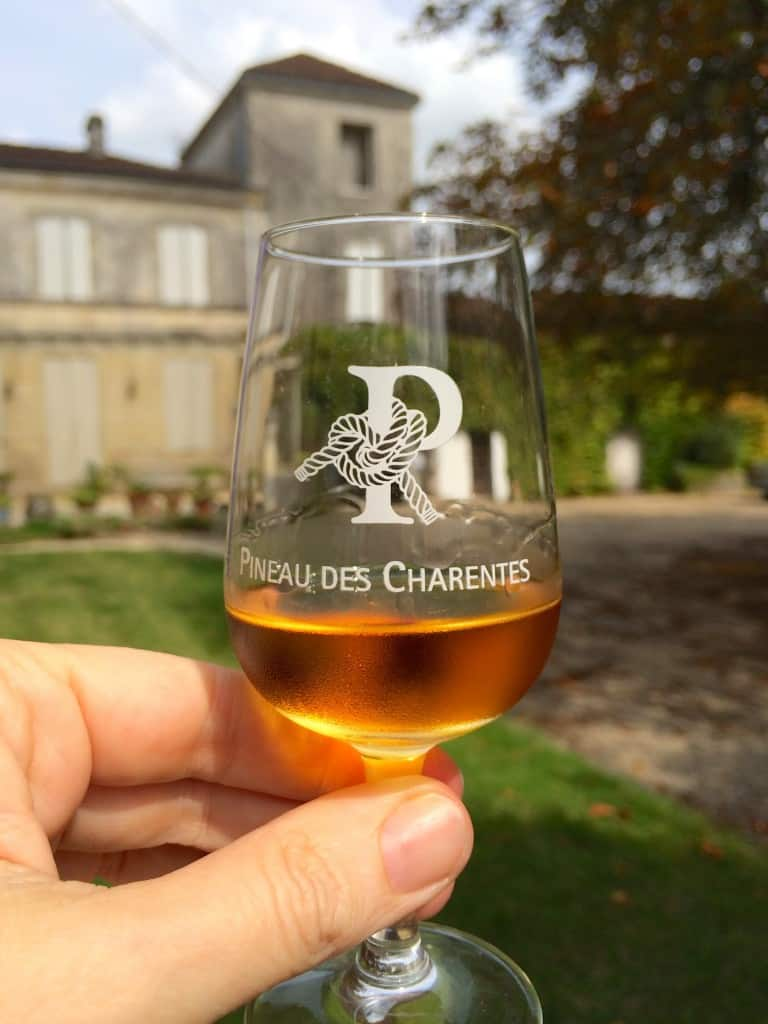 glass of pineau outside Chateau Guynot