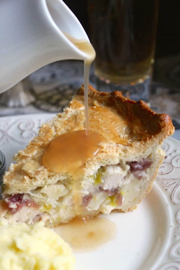 Pouring gravy on Chicken, Brie and Cranberry pie.