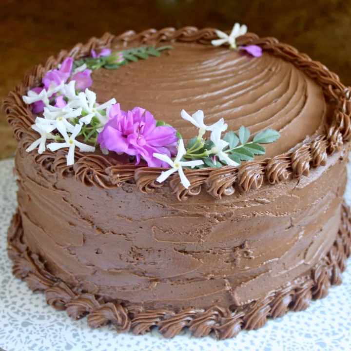 moist chocolate cake recipe with edible flowers on top