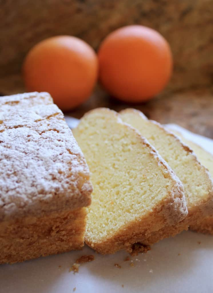 Best gluten free orange pound cake sliced on plate with oranges behind.