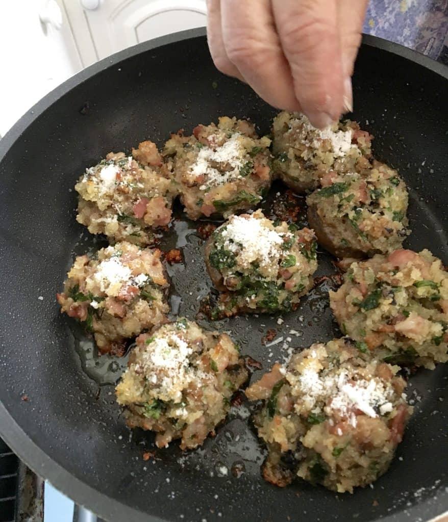 Adding real cheese to stuffed mushrooms.