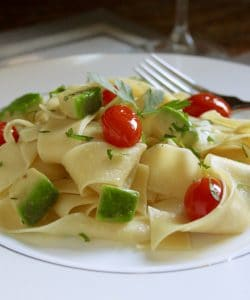 Egg pasta dish with avocado and tomatoes