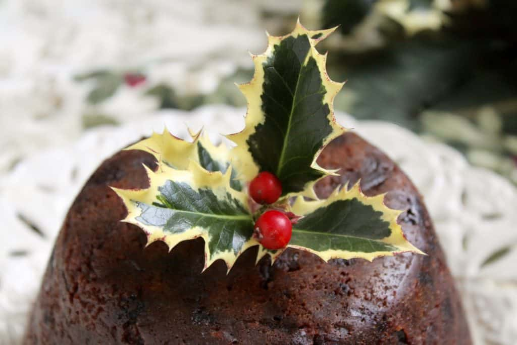 close up of holly on top of a Christmas pudding