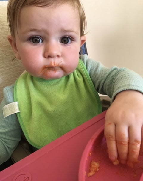 Baby eating gnocchi for the first time.
