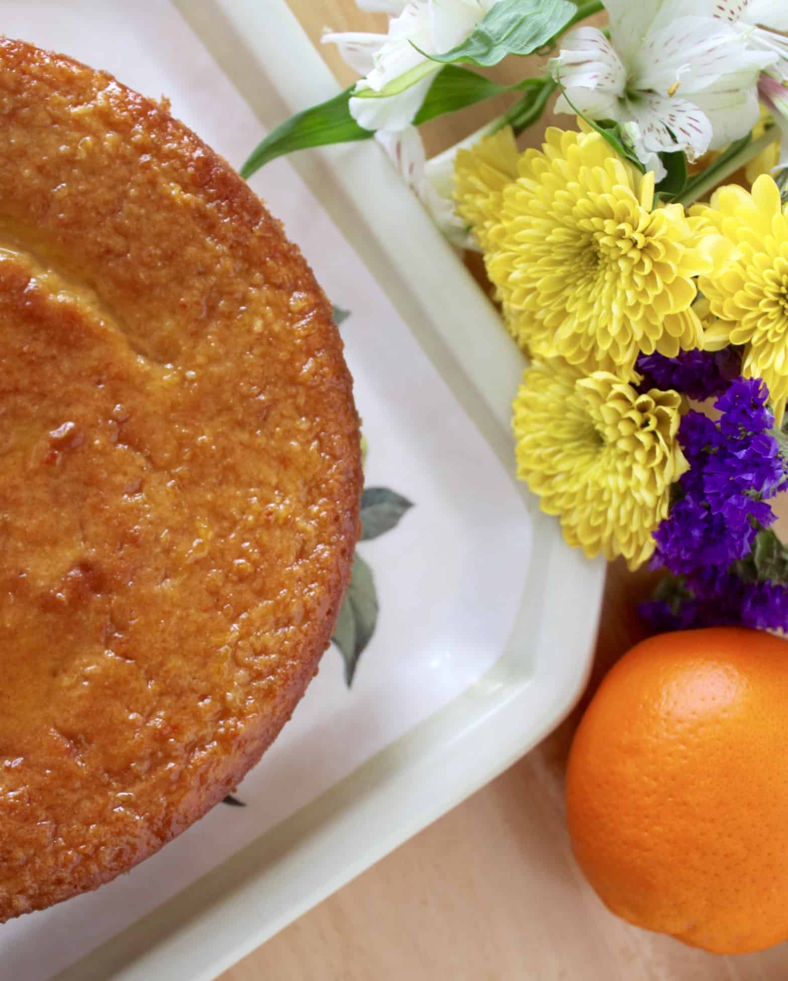 Sicilian Orange Cake on a plate with orange and flowers