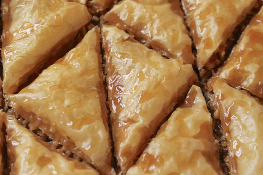 pieces of baklava in tray with honey on top