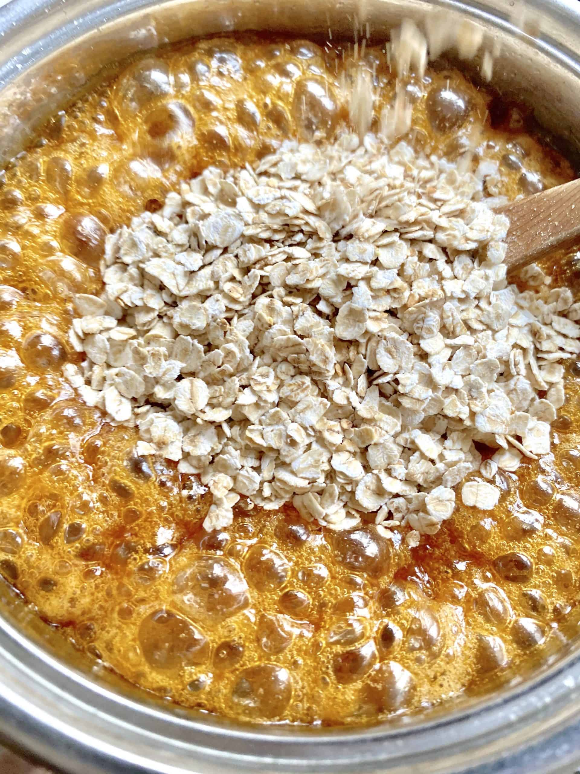 adding oats to bubbling sugar syrup