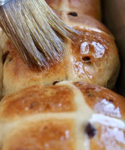 brushing hot cross buns with glaze
