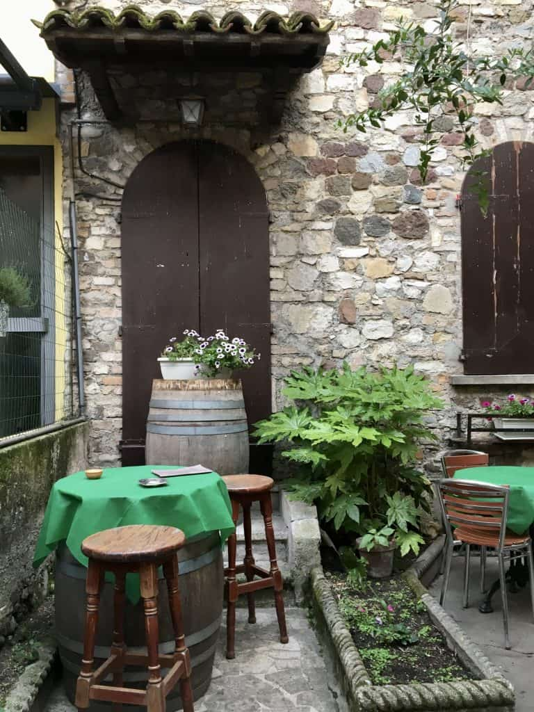 Pretty outdoor area with barrel, table and chairs in Sirmione