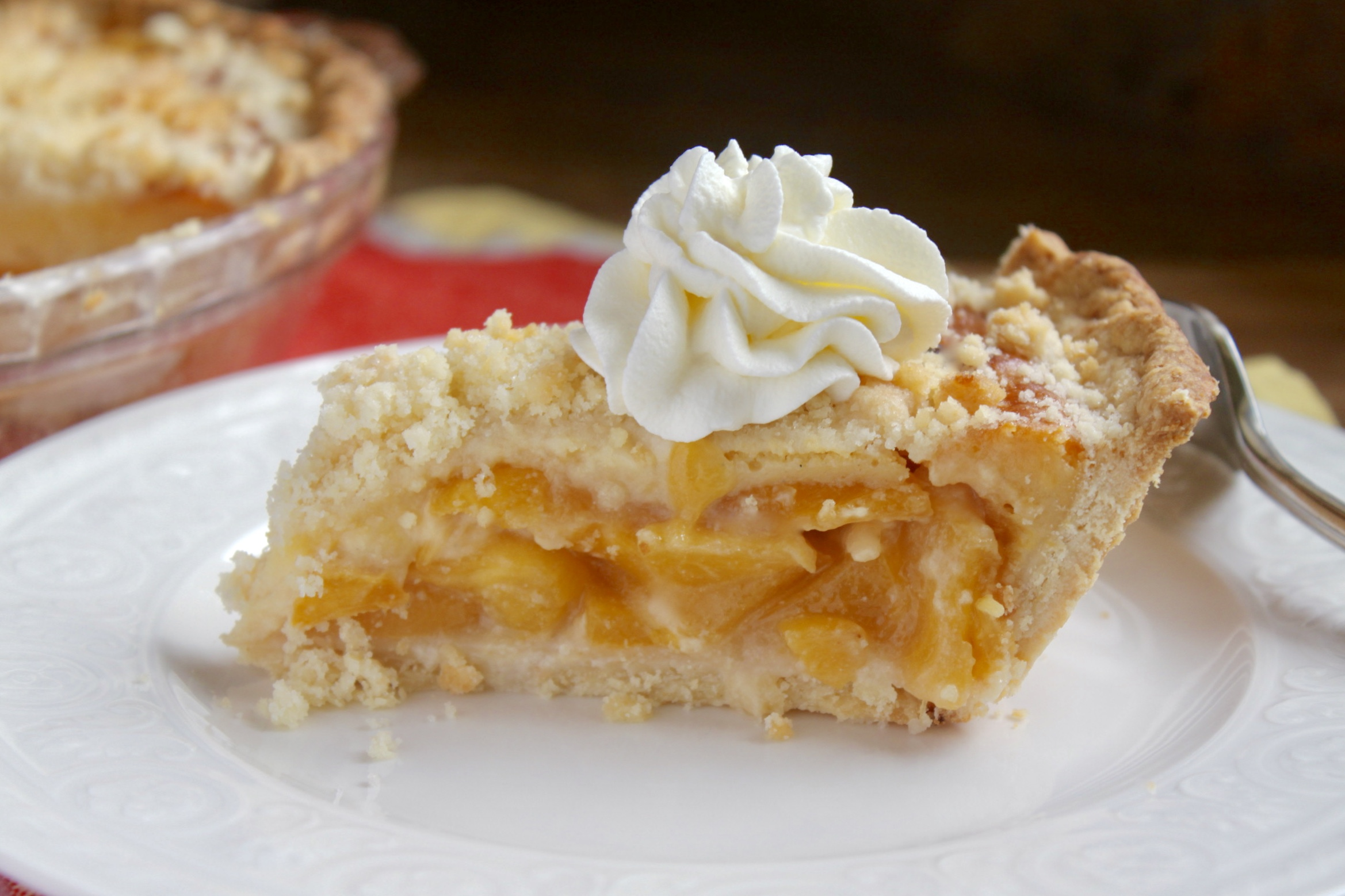 Slice of custard peach pie with whipped cream