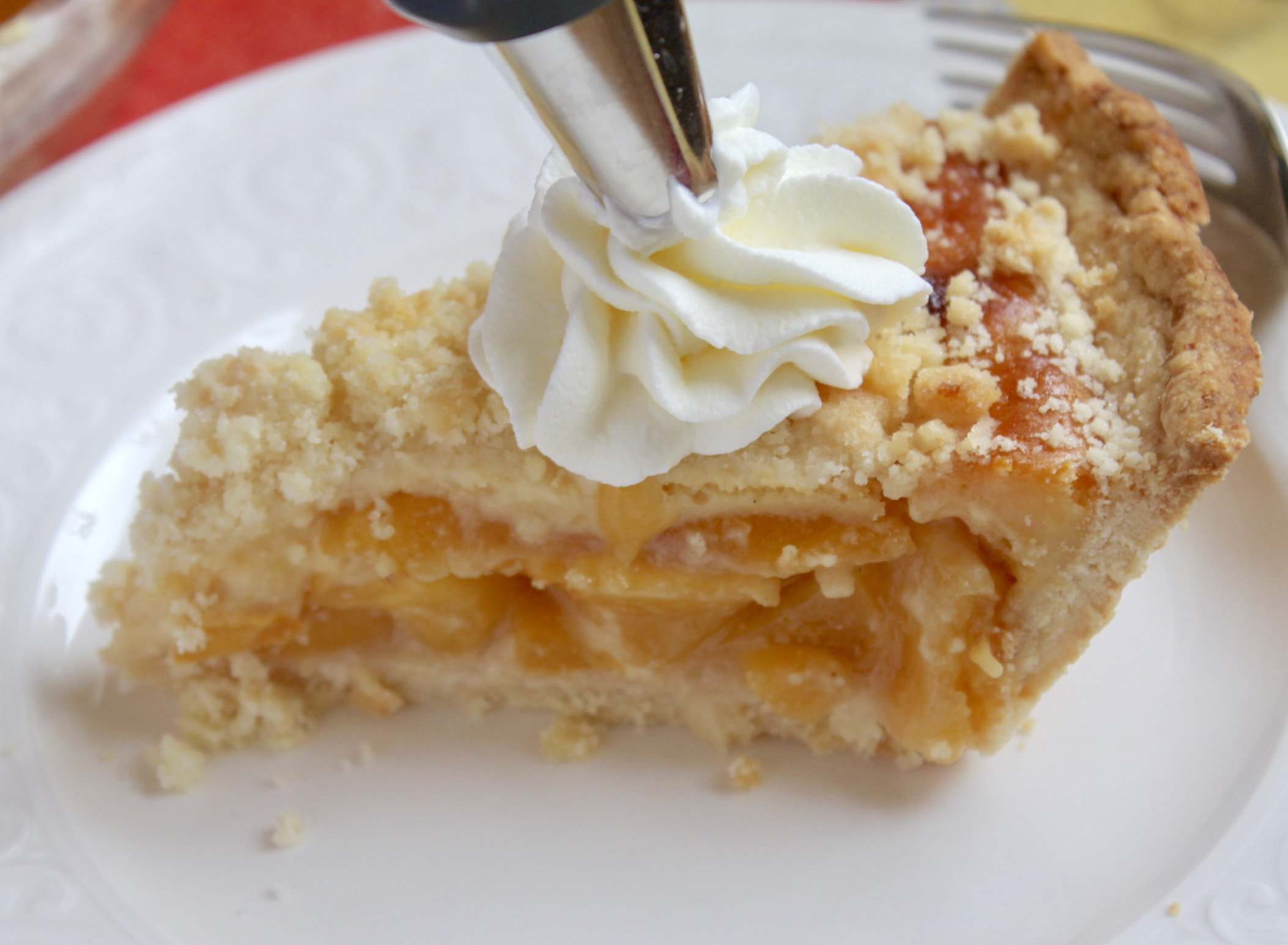 adding cream to slice of custard peach pie